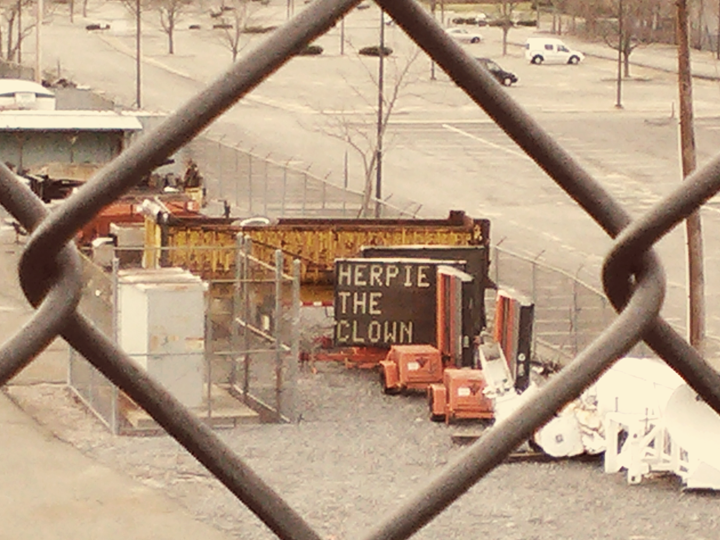 programmable highway sign, parked in storage yard, message reads &quot;herpie the clown&quot;